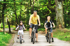 Família feliz no bicicletas no campo Fotografia de Stock Royalty Free