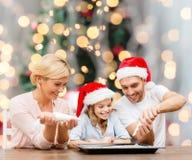Família feliz no cozimento dos chapéus do ajudante de Santa Fotografia de Stock