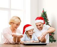 Família feliz no cozimento dos chapéus do ajudante de Santa Fotografia de Stock Royalty Free