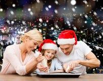 Família feliz no cozimento dos chapéus do ajudante de Santa Fotos de Stock
