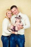 Família feliz no fundo bege Pais novos foto de stock royalty free