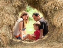 Família feliz no monte de feno fotografia de stock royalty free