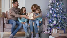 Família feliz no Natal, no mum, no paizinho e nas duas meninas sentando-se em casa no sofá perto da árvore de Natal para abrir filme