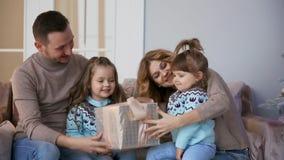 Família feliz no Natal, no mum, no paizinho e nas duas meninas sentando-se em casa no sofá perto da árvore de Natal para abrir video estoque