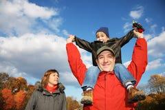 Família feliz no parque do outono Fotos de Stock Royalty Free