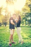 Família feliz no parque, mãe e pai que guardam e que beijam alguns meses filho idoso, criança Retrato infantil e conceito de famí Fotos de Stock Royalty Free