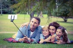 Família feliz no parque que toma o selfie Fotografia de Stock Royalty Free