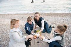 Família feliz no piquenique pela costa de mar no tempo nublado Fotografia de Stock Royalty Free