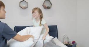 A família feliz no quarto na manhã, duas crianças que lutam descansos sobre o sorriso feliz parents o encontro na cama filme