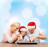 Família feliz nos chapéus do ajudante de Santa que fazem cookies Imagem de Stock