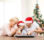 Família feliz nos chapéus do ajudante de Santa que fazem cookies Fotografia de Stock Royalty Free