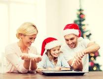 Família feliz nos chapéus do ajudante de Santa que fazem cookies Imagem de Stock Royalty Free