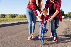 Família feliz nova com as crianças que têm o divertimento na natureza As crianças felizes montam o 'trotinette' no parque imagem de stock