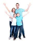 A família feliz nova com crianças levantou as mãos acima