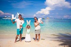 A família feliz nova e duas crianças com palavra AMAM sobre Imagem de Stock