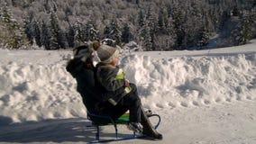 A família feliz nova está tendo o divertimento que joga na mamã nevado da floresta rola seu pouco filho em um trenó Mamã e seu fi video estoque