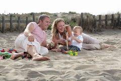 Família feliz nova na praia fotos de stock royalty free