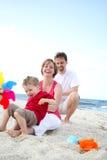 Família feliz nova na praia imagens de stock