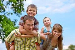 A família feliz nova que dá dois filhos anda às cavalitas passeios Imagem de Stock Royalty Free