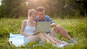Família feliz nova que olha o portátil e que ri no parque com luz solar surpreendente filme