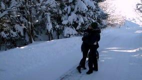 A família feliz nova que tem o divertimento que joga em pais nevados de uma floresta rola seu pouco filho em um trenó Beijo dos p filme