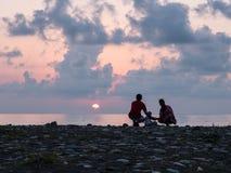 Família feliz - o pai, mãe, filho do bebê vê a ressaca do mar do por do sol na praia preta da areia Pais ativos e povos exteriore fotos de stock royalty free