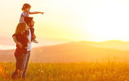 Família feliz: pai da mãe e filha da criança no por do sol