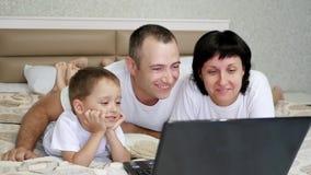 Família feliz: pai, mãe e bebê, encontrando-se na cama, olhando o portátil, sorrindo e rindo no movimento lento vídeos de arquivo