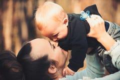 Família feliz para apreciar o dia ensolarado Filho pequeno do beijo da mãe com amor Jogo da mulher com criança Mamã e bebê exteri imagens de stock