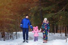 Família feliz, pares novos e sua filha passando o tempo exterior no inverno imagem de stock royalty free