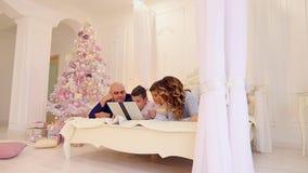 A família feliz passa felizmente o tempo junto e usa o computador, encontrando-se na cama no quarto brilhante com árvore de Natal vídeos de arquivo