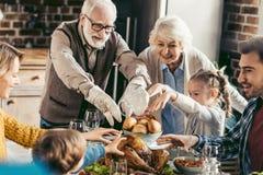 família feliz que alcança para o peru Fotografia de Stock