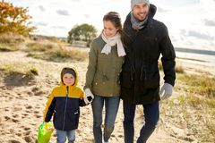 Família feliz que anda ao longo da praia do outono fotografia de stock