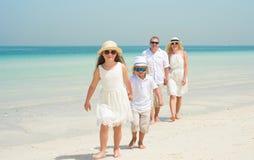 Família feliz que anda ao longo de uma praia Imagens de Stock Royalty Free