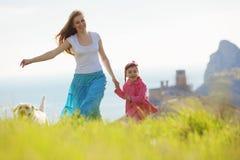 Família feliz que anda com cão Imagens de Stock Royalty Free