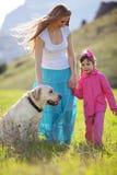 Família feliz que anda com cão Fotografia de Stock Royalty Free