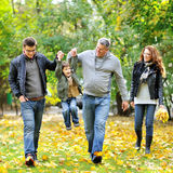 Família feliz que anda junto em um parque imagens de stock