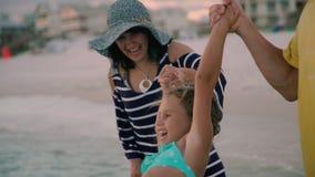 A família feliz que anda na costa do oceano mostra em silhueta o por do sol vídeos de arquivo