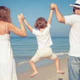 Família feliz que anda na praia no tempo do dia Imagens de Stock