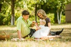 Família feliz que anda no parque Fotos de Stock Royalty Free