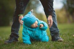 Família feliz que anda no parque do outono: a criança tenta provar que não pode tentar fotos de stock