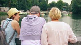 Família feliz que aprecia férias Os sêniores e sua filha adolescente estão pelo lago no parque que sightseeing video estoque