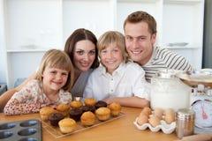 Família feliz que apresenta seus queques imagem de stock