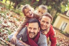 Família feliz que coloca na terra, poses à câmera Imagens de Stock Royalty Free