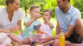 Família feliz que come frutos no piquenique no parque filme