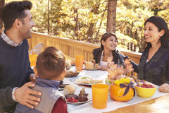 Família feliz que come na tabela em uma plataforma em uma floresta foto de stock royalty free