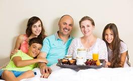 Família feliz que come o café da manhã na cama imagem de stock