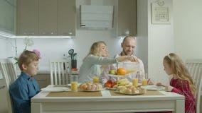 Família feliz que come o café da manhã saudável na cozinha filme