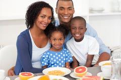 Família feliz que come o pequeno almoço saudável
