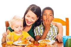 Família feliz que come a pizza foto de stock